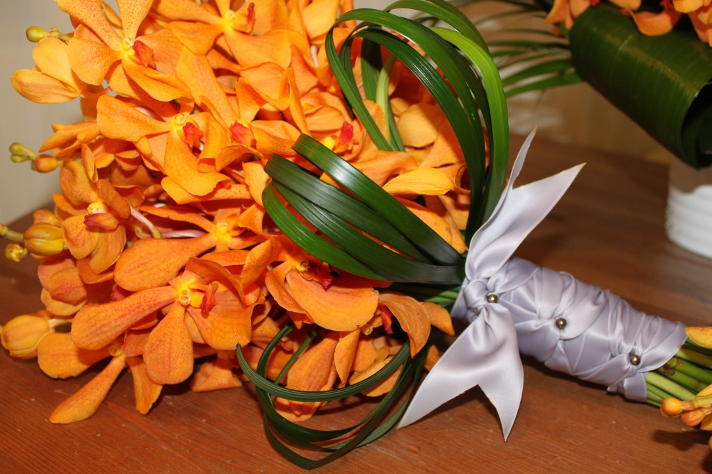 Orange mokara orchid bouquet with lily grass loops