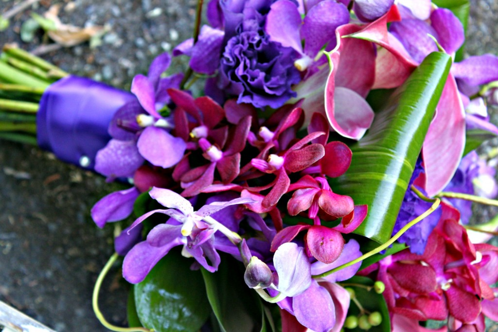 Orchids and lisianthus with tropical foliage wedding bouquet